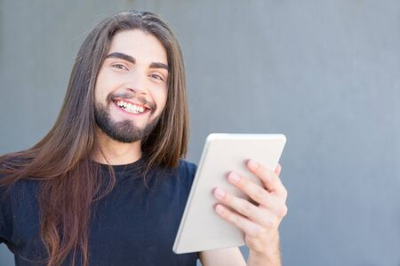 Happy young bearded man posing with tablet. Smiling brunet with piercing holding tablet and looking at camera. Technology concept