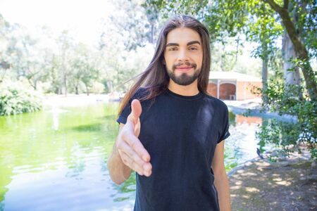 Smiling young man with piercing stretching hand to camera. Cheerful guy with long hair standing on lake shore. Handshake concept Stock Photo - 127324766