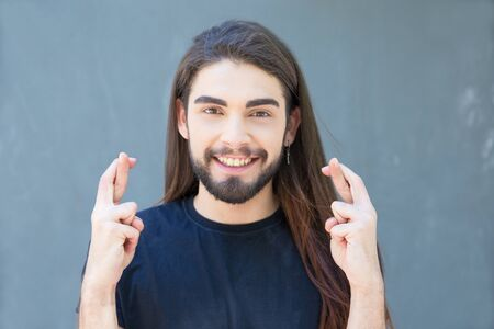 Smiling young bearded man with piercing holding cross fingers. Stylish brunet with long hair and piercing in nose gesturing. Concept of good luck or nullify promise t of good luck or nullify promise
