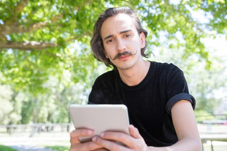 Serious man with tablet looking at camera. Thoughtful young brunet with tablet posing in park. Technology concept