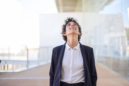 Happy businesswoman looking up. Cheerful middle aged woman in formal wear standing and smiling, looking up. Emotion concept Foto de archivo
