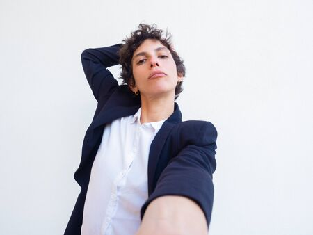 Confident androgynous young woman holding cell phone in hand and taking selfie. Self portrait of female professional in office suit. Poser concept Standard-Bild