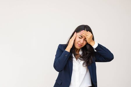 Tired young businesswoman having headache. Stressed young woman in formal wear suffering from headache isolated on grey background. Emotion concept