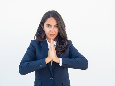 Serious calm businesswoman making Namaste gesture. Young Latin woman in office suit practicing meditation. Stress relief concept Stock Photo