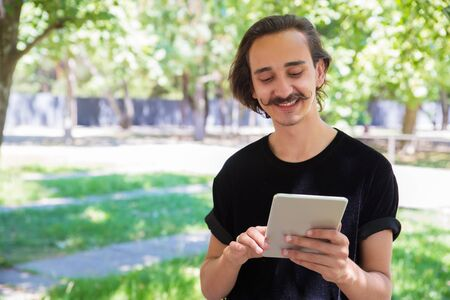 Smiling man using tablet pc outdoor. Handsome happy man standing in park and using digital tablet. Wireless technology concept Stockfoto