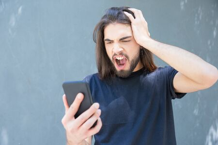 Angry young brunet looking at phone and screaming. Bearded man with piercing and long hair yelling at smartphone. Technology concept
