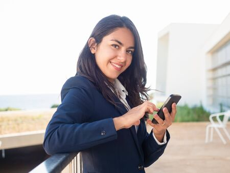 Cheerful young businesswoman using mobile internet app outside. Beautiful young Latin woman in office suit holding smartphone and smiling at camera. Online app concept