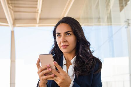 Young woman using mobile phone. Beautiful brunette woman using smartphone and looking away. Technology concept Фото со стока