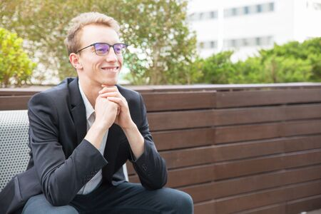 Cheerful manager enjoying work break outside. Happy young business man in eyeglasses and jacket sitting on bench, leaning chin on hands, looking away and smiling. Business portrait concept