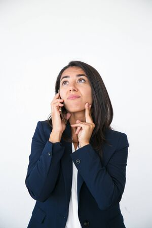 Pensive excited business woman talking on phone and studying information overhead. Young Latin woman speaking on cellphone and looking up. Presenting concept