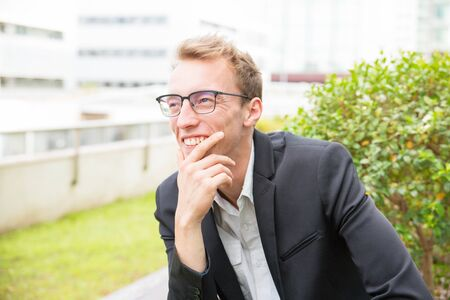 Cheerful happy office worker enjoying outdoor work break. Young business man in eyeglasses and jacket sitting outside, leaning chin on hand, looking away and smiling. Good news concept Banco de Imagens