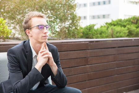 Pensive professional thinking over project. Thoughtful young business man in eyeglasses and jacket sitting outside, leaning chin on hands and looking into distance. Pensive businessman concept