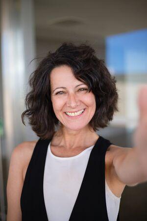 Selfie de mujer de pelo rizado alegre feliz en casual. Señora de mediana edad emocionada sosteniendo el teléfono inteligente y tomando una foto de sí misma. Concepto de retrato de mujer feliz Foto de archivo