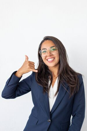 Happy businesswoman asking for call. Beautiful young businesswoman showing call me gesture and smiling at camera isolated on grey background. Communication concept