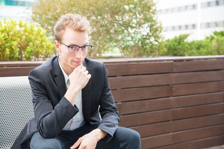 Cheerful pensive office employee posing outdoors. Young business man in eyeglasses and jacket sitting on bench outside, leaning chin on hand and looking at camera. Businessman outside concept