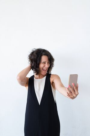 Excited joyous woman taking selfie in studio. Cheerful middle aged woman holding smartphone, touching hair, smiling and grinning at phone camera. Selfie concept