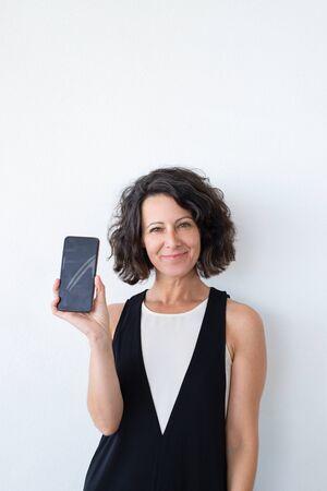 Felice donna sicura di sé che fa pubblicità all'app mobile online. Gioiosa donna dai capelli ricci di mezza età in casual che mostra lo schermo del telefono vuoto in telecamera. Concetto di app mobile