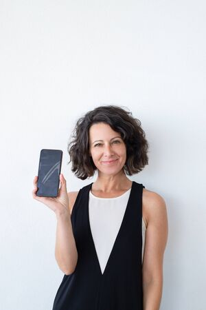 Happy confident woman advertising online mobile app. Joyful middle aged curly haired woman in casual showing blank phone screen at camera. Mobile app concept