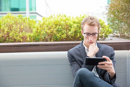 Pensive professional watching video on smartphone. Young business man in eyeglasses and jacket sitting outside, leaning chin on hand and using cell. Wireless technology concept