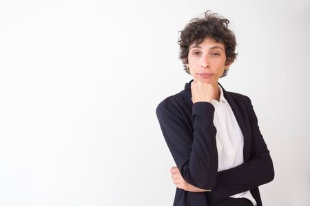 Bored middle aged businesswoman. Portrait of serious businesswoman with short hair standing with hand on chin and looking at camera. Emotion concept Banco de Imagens