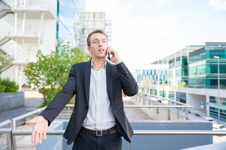 Serious puzzled manager talking on cell outside. Young business man standing near city business center, calling on mobile phone and making confused gesture. Communication concept Imagens