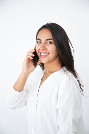 Smiling confident woman speaking on cell. Happy beautiful young Latin woman in white shirt calling on mobile phone. Phone talk concept Фото со стока