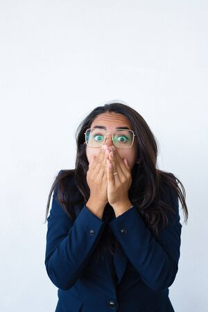 Scared terrified business woman feeling stressed. Shocked beautiful young Latin woman office jacket covering mouth with hands and staring at camera with wide eyes. Panic or fear concept