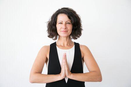 Lächelnde friedliche Frau in lässigem Yoga und Meditation. Ruhige Frau mittleren Alters, die Namaste-Geste macht und in die Kamera schaut. Yoga-Konzept