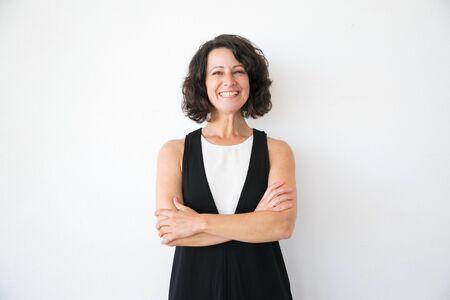 Glückliche frohe Frau in der zufälligen Aufstellung über weißem Studiohintergrund. Porträt einer fröhlichen, erfolgreichen Geschäftsfrau mittleren Alters mit verschränkten Armen lächelnd in die Kamera. Konzept des weiblichen Porträts