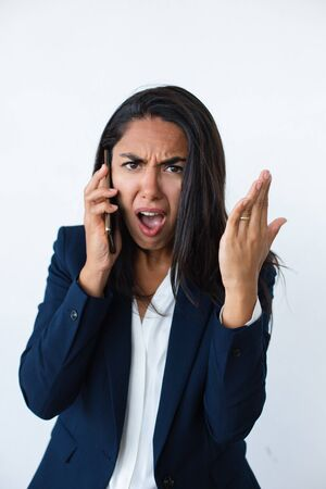 Unhappy businesswoman talking by smartphone. Angry young woman having unpleasant phone talk and looking at camera. Connection concept