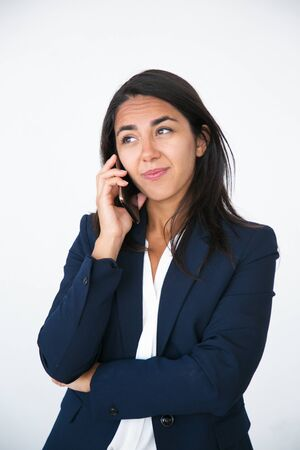 Pensive business woman thinking over solution while talking on cell. Young Latin woman in office jacket speaking on mobile phone with thoughtful face. Decision making concept