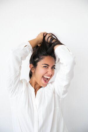 Mujer emocionada llena de alegría que se regocija por las buenas noticias y se divierte. Feliz joven latina en camisa blanca sosteniendo el cabello por encima, sonriendo y gritando de alegría. Concepto de alegría Foto de archivo