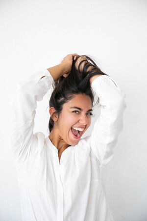 Overjoyed excited woman rejoicing at good news and having fun. Happy young Latin woman in white shirt holding hair overhead, smiling and shouting for joy. Joy concept Stock Photo