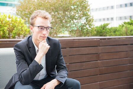 Pensive serious manager thinking over project outside. Young business man in eyeglasses and jacket sitting on bench, leaning chin on hand and looking away. Pensive businessman concept Banco de Imagens