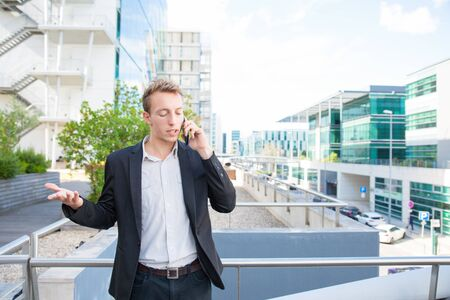 Stressed annoyed business man talking on mobile phone outside. Young office worker standing near city business center, calling on cell and making irritated gesture. Phone talk and problem concept Foto de archivo