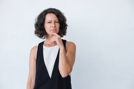 Pensive middle aged woman. Portrait of serious thoughtful woman holding hand on chin and looking at camera isolated on grey background. Emotion concept