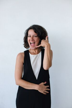 Excited woman asking for call. Happy middle aged woman showing call me symbol and smiling at camera isolated on grey background. Gesture concept 스톡 콘텐츠