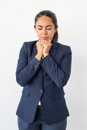 Nervous young woman with closed eyes. Portrait of young businesswoman standing with closed eyes and hands near chin isolated on grey background. Emotion concept