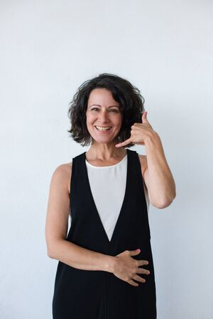 Happy woman asking for call. Cheerful middle aged woman with curly hair showing call me gesture and smiling at camera. Communication concept Stok Fotoğraf