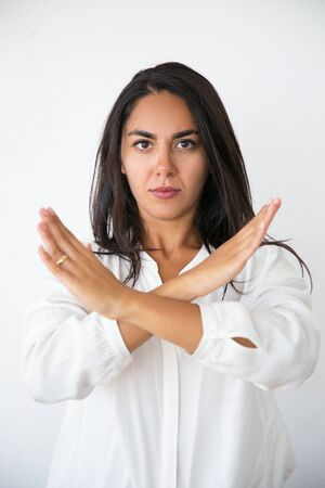 Serious strict woman showing prohibition sign. Beautiful young Latin woman in white shirt crossing arms in restrictive gesture. Prohibition concept