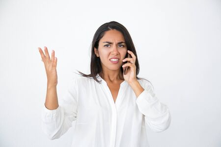 Annoyed beautiful woman speaking on phone. Angry young Latin woman in white shirt making displeased face and gestures and talking on cell. Feeling stressed concept 免版税图像