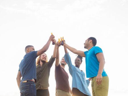 Lächelnde Freunde, die mit Bierflaschen im Park stehen und jubeln. Gruppe junger Leute, die sich nach der Arbeit entspannen. Feierkonzept