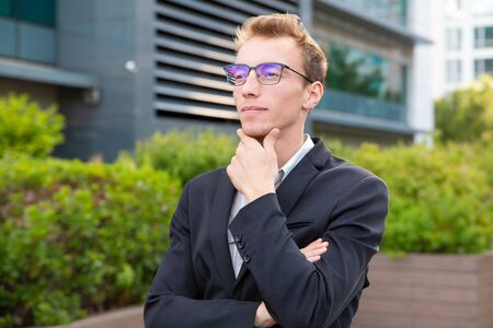 Pensive confident businessman thinking over business strategy. Portrait of handsome young man in office jacket touching chin and looking into distance. Business portrait concept