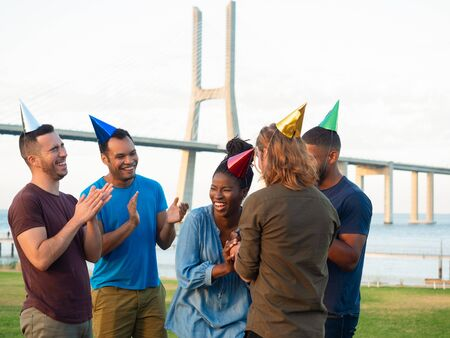 Happy people in paper hats celebrating in park. Cheerful young friends having fun at nature. Concept of birthday party