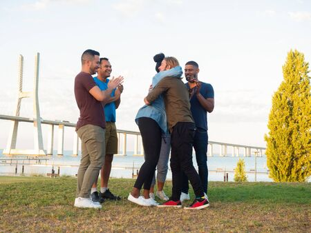 Happy woman with dreadlocks hugging bearded guy. Group of smiling young people standing in circle together. Concept of friendship Banco de Imagens