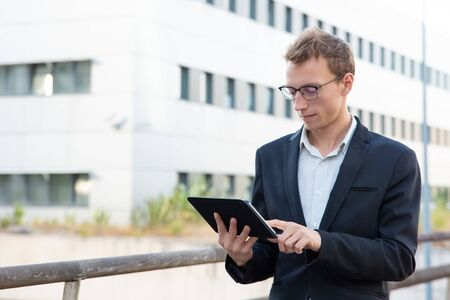 Positive focused professional working on tablet outside. Young business man standing outside, using tablet and touching screen. Mobile computer concept