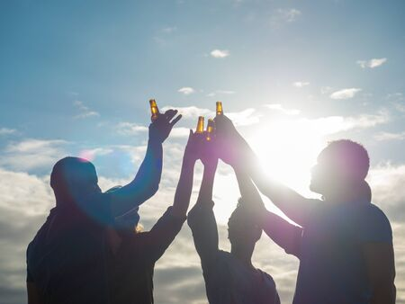 Cropped shot of friends clinking beer bottles and dancing. Group of young people relaxing after work. Celebration concept Standard-Bild