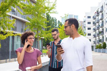 Pareja alegre con teléfonos móviles hablando entre sí. Dos hombres sosteniendo smartphone, mujer con café hablando por teléfono móvil y riendo. Concepto de tecnología móvil
