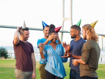 Smiling friends making surprise for young woman. Cheerful young people covering eyes of beautiful African American woman. Concept of birthday party