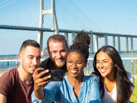 Lächelnde Männer und Frauen, die Selfie im Freien machen. Fröhliche junge multiethnische Freunde, die Selfie mit Smartphone im Park machen. Technologiekonzept